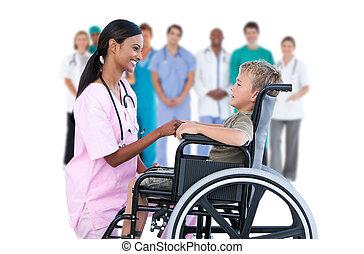 Nurse chatting with little boy in wheelchair