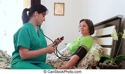 Nurse checking senior woman blood pressure at home. Focus on patient.