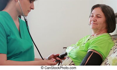 Nurse checking blood pressure - Nurse checking senior woman...