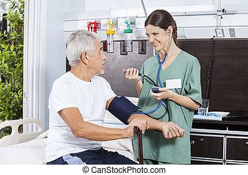 Nurse Checking Blood Pressure Of Senior Man In Rehabilitation Ce