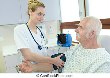 nurse checking hospital patients blood pressure