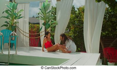 Nurse checking woman's scraped knee by pool - Caring nurse ...