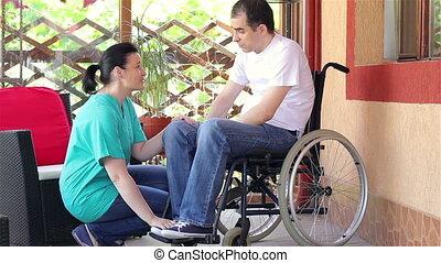 Nurse consoling disabled sad man