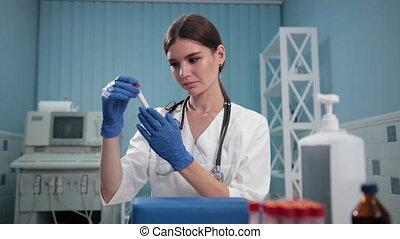 nurse doctor holding a test tube, carefully examines it