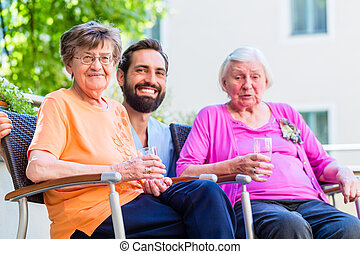 Nurse drinking coffee with seniors on terrace