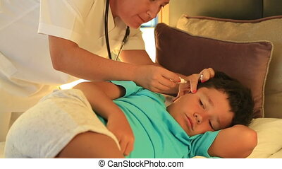 Nurse dripping eardrops to child in bed room - Female doctor...