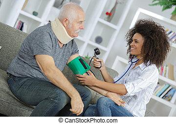 nurse examining blood pressure of senior man at home
