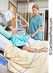 Nurse examining male patient lying on bed in hospital