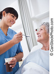 Nurse feeding a patient in hospital ward