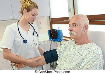 nurse getting the patients blood pressure