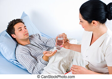Nurse give pils and water to a patient