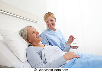 nurse gives the pill to the elderly woman patient lying in the hospital room bed, concept of loneliness and old age diseases
