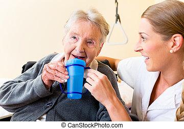Nurse giving drink to elderly woman in wheelchair