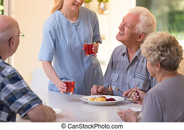 Nurse giving juice to seniors - Nurse in uniform giving...