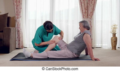Nurse giving leg massage to senior woman in a retirement home