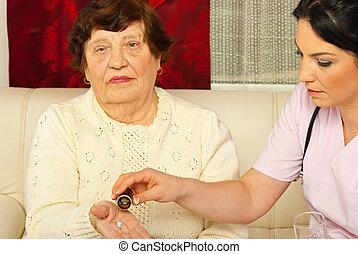 Nurse giving medicines to elderly woman