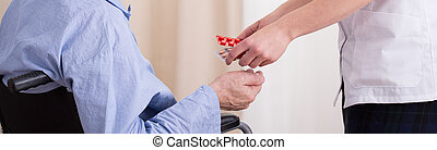 Nurse giving patient medicament - Nurse's hands giving...