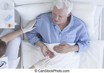 Nurse giving patient tablets at hospital - Nurse giving sick...