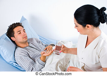 Nurse giving pills to a male patient
