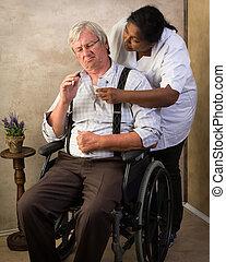 Nurse giving pills to elderly man