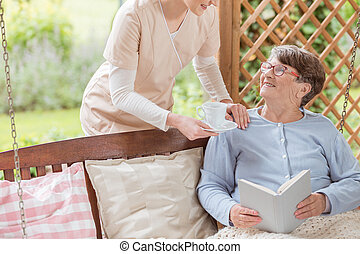 Nurse giving tea to happy elderly woman reading book on the terrace