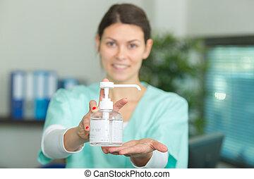 nurse hands showing sanitizer dispenser in washroom
