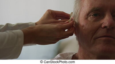 Close up of a senior Caucasian man at a retirement home, sitting and being fitted with a hearing aid by a Caucasian female nurse, during coronavirus covid19 pandemic.