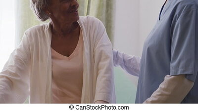 A Caucasian nurse wearing blue scrubs, helping a senior African American woman walking with a walking frame, in a retirement home, during coronavirus covid19 pandemic.