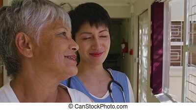 Close up of senior mixed race woman standing in the corridor at a retirement home with a Caucasian female doctor, looking out of the window on a sunny day, during coronavirus covid19 pandemic.
