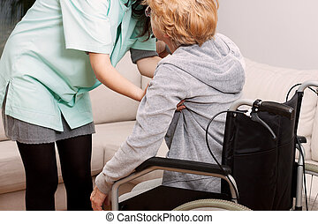 Nurse helping disabled woman