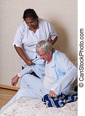 Nurse helping elderly man getting dressed - Nurse in nursing...