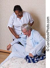 Nurse helping elderly man getting dressed