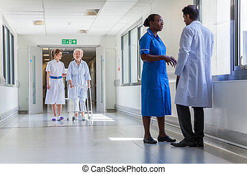 Nurse Helping Elderly Old Female Patient in Hospital Corridor with Doctor