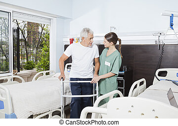 Nurse Helping Male Patient In Using Walker At Nursing Home