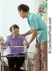 Nurse helping older lady - Young pretty nurse helping older...