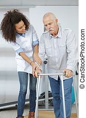 Nurse helping patient walk with a frame