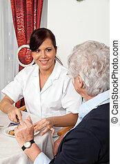 Nurse helping senior citizen at breakfast