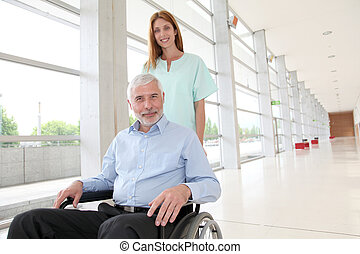Nurse helping senior man in wheelchair