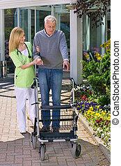 Nurse Helping Senior Man with Walker Outdoors