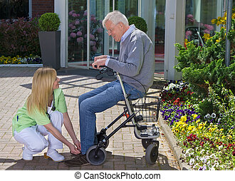 Nurse Helping Senior Man with Walker to Tie Shoes
