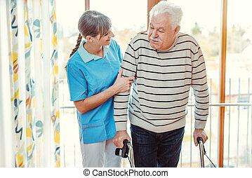 Nurse helping senior man with walking frame in nursing home