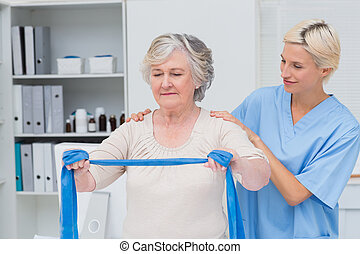 Nurse helping senior patient in exercising with resistance band