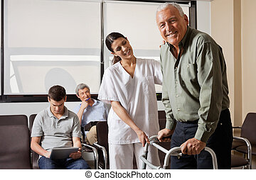 Nurse Helping Senior Patient With Walker - Portrait of...