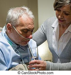 Nurse helping senior sick man with drinking