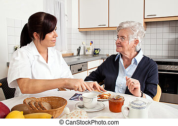 nurse helps elderly woman at breakfast - a geriatric nurse...