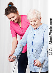Nurse helps to walk the old woman