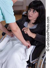 Nurse helps woman on wheelchair
