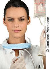 nurse holding a drip bag