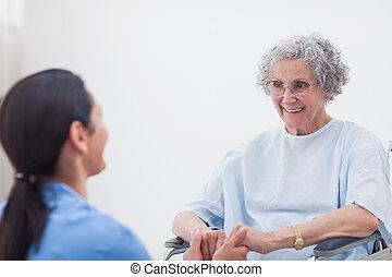Nurse holding hands of a patient