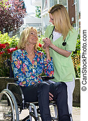 Nurse Holding Hands with Senior Woman in Garden